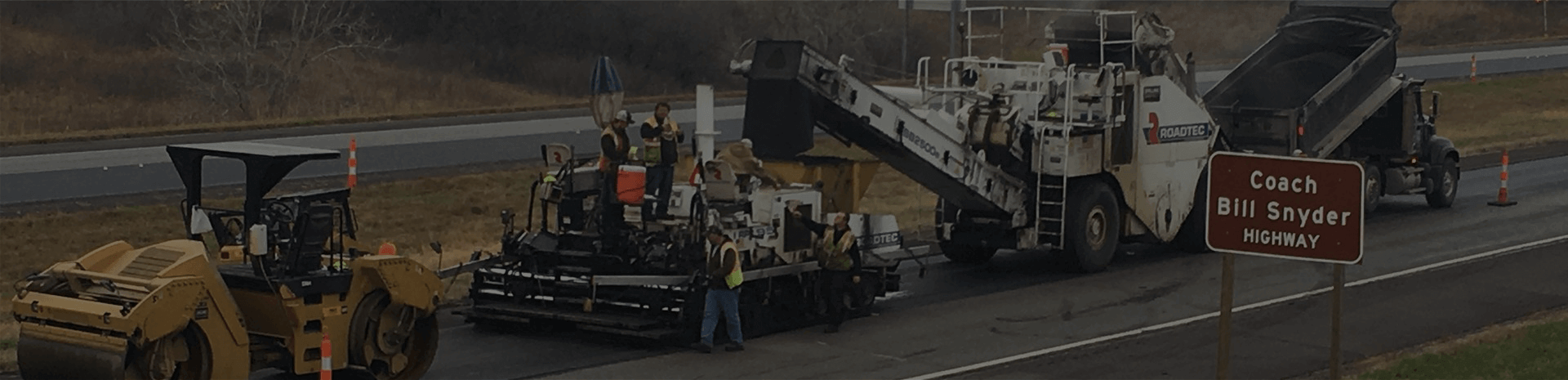 photo of paving operation in-progress on coach bill snyder highway